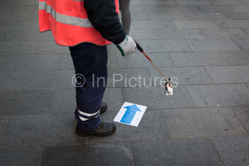 A street cleaning contractor uses a pick-up tool to remove a blue arrow on the ground in Leicester Square, on 13th November 2018, in London, England.
