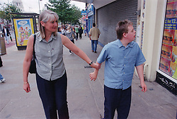 Mother walking along street holding arm of teenage son with Downs Syndrome,