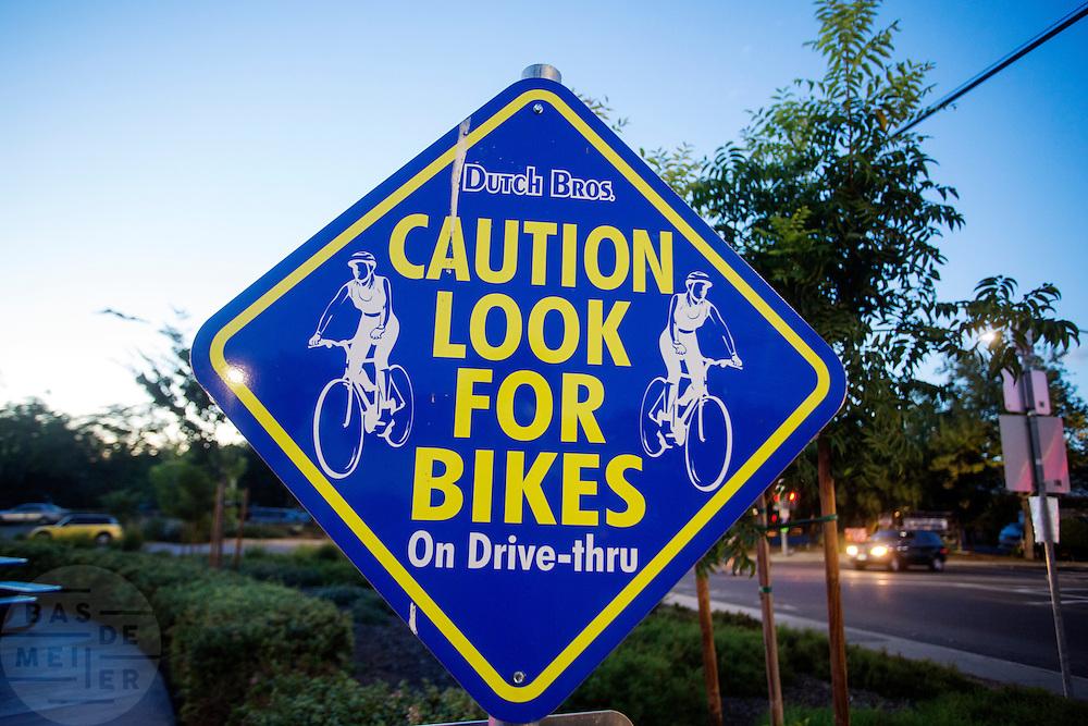 In de Amerikaanse plaats Davis, California waarschuwt een bord bij een drive-in koffieshop voor passerende fietsers.<br /> <br /> In the American town Davis, California a sign at a drive-thru coffee shop warns for passing cyclists.