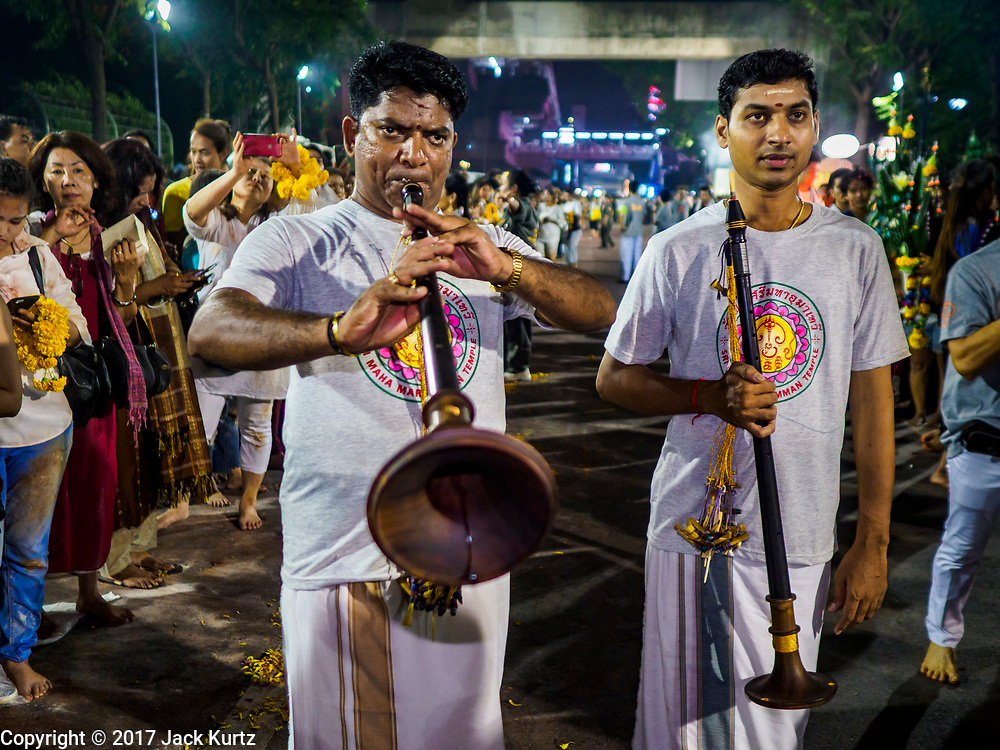 30 SEPTEMBER 2017 - BANGKOK, THAILAND: Musicians accompanying the chariot bearing the deity perform during the Navratri parade in Bangkok. Navratri is a nine night (10 day) long Hindu celebration that marks the end of the monsoon and honors of the divine feminine Devi (Durga). The festival is celebrated differently in different parts of India, but the common theme is the battle and victory of Good over Evil based on a regionally famous epic or legend such as the Ramayana or the Devi Mahatmya. Navratri is celebrated throughout Southeast Asia in communities that have large Hindu population. Bangkok's celebration of Navratri was subdued this year because Thais are still mourning the death of Bhumibol Adulyadej, the Late King of Thailand, who died on October 13, 2016.      PHOTO BY JACK KURTZ