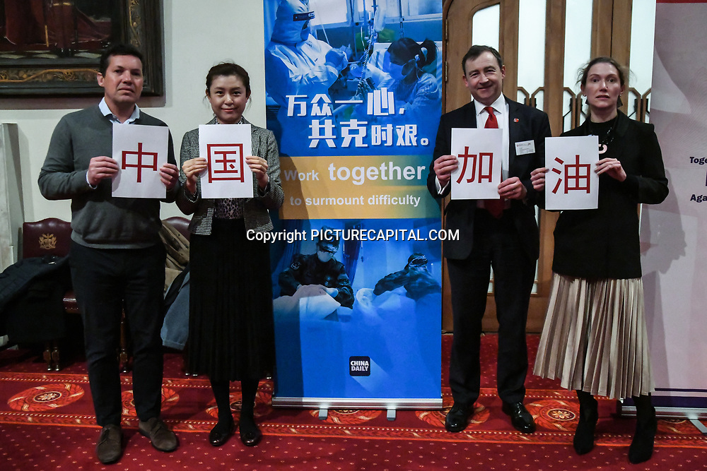 Attendees holding with Chinese characters(中国加油 - Go China!) at China-UK United We Stand together to fights the #Covid19 at Guildhall, on 28th February 2020, London, UK.