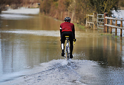 © Licensed to London News Pictures. 27 January 2013. Ascott Under Wychwood, Oxfordshire. Cyclist pedals down a flooded road. Floods after the snow melted. Photo credit : MarkHemsworth/LNP