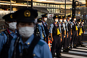 Police officers stand in a line to stop the traffic outside the Tokyo Metropolitan Gymnasium in Tokyo on July 23, 2021 ahead of the opening ceremony of the Tokyo 2020 Olympic Games. (Photo by Yuki IWAMURA / AFP)