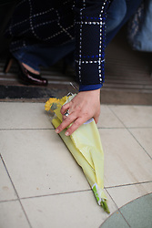 "© Licensed to London News Pictures . 11/03/2014. A woman picks up floral tributes left at the RMT head office, London, to paid tribute to Bob Crow, General secretary of the Rail Maritime and Transport union, who has died today (11/03/14) at the age of 52 of a heart attack. The more reads: ""The last truly great union leader. Condolences to your family and members. Linda and Joan, GMB members."" London, UK.   Photo credit: Isabel Infantes /LNP"