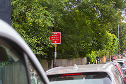 A tree's branches partially obscure a sign indicating a new road layout ahead in Southgate, North London. Overgrown trees and other roadside clutter are obscuring motorists' views of roadsigns that often impart crucial speed or safety information only at the last minute. London, July 17 2019.