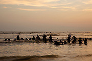 Groups of people swimming and playing in the waves in the Bay of Bengal sea during sunset on Laboni Beach, Cox Bazar, Chittagong Division, Bangladesh, Asia. The sun is setting behind clouds in the sky and the horizon is warm with an orange glow.  (photo by Andrew Aitchison / In pictures via Getty Images)