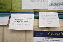 Advert in Polish language advertising various services displayed in Polish shop,