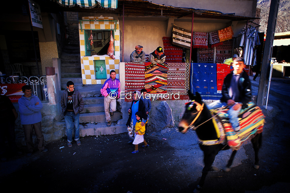 Trekking mule, carpet shop and villagers on a street in Imlil, High Atlas, Morocco.