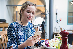 Young woman using mobile phone while sitting at restaurant
