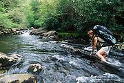 Backpacker fording Snowbird Creek, spring, Snowbird Area, Nantahala National Forest, North Carolina