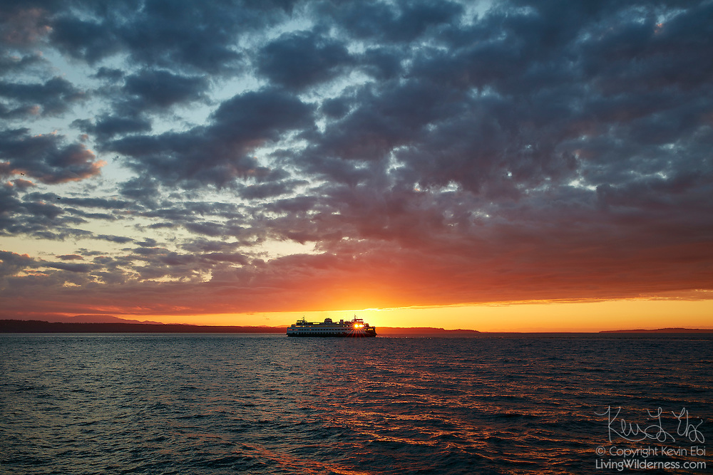 The setting sun shines through the windows of a Washington State Ferry as it crosses Puget Sound from Edmonds, Washington under cloudy skies.