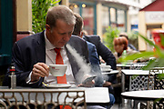 A businessman wearing a dark suit and an orange tie using an e-cigarette at a cafe at Leadenhall Market on the 24th September in London in the United Kingdom.