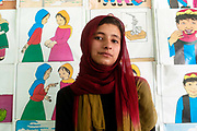 Afghanistan. Mazar-e-Sharif high school. Girl aged 14, standing in front of Save the Children posters.