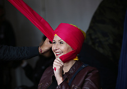 A woman has a turban tied during during the Mayor of London Vaisakhi celebrations in Trafalgar Square, London, to mark the Sikh New Year.