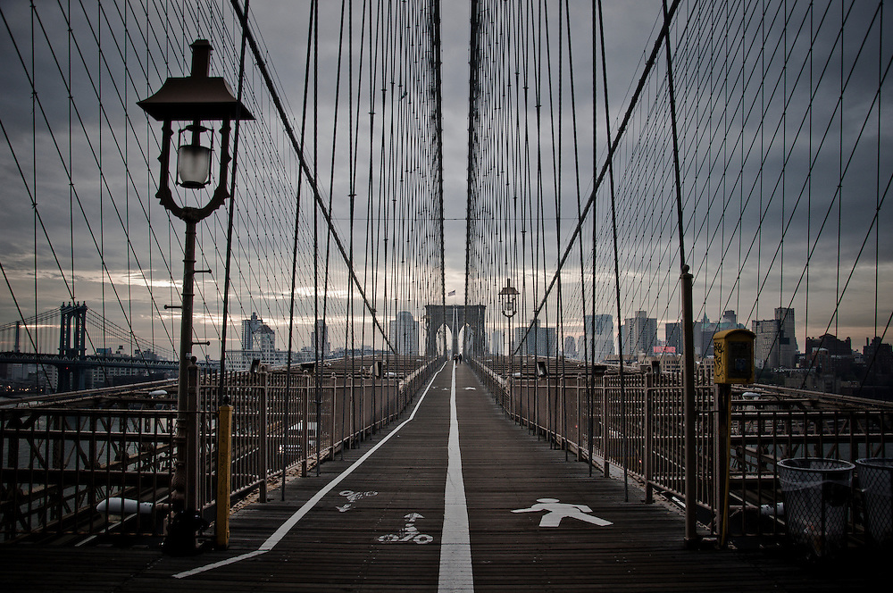 Panorama of the Brooklyn Bridge path surrounded by a wab of cables, Manhattan, New York.