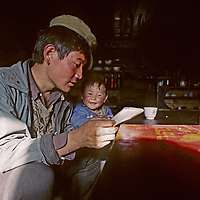 CHINA, TIBET.  Young father & son, reading at home in Pe village, near Tsangpo River Gorge.