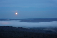 Greenville, New York  - The full moon sets over fog covering the Neversink Valley and Delaware Valley on  Dec.10, 2011. ©Tom Bushey / The Image Works