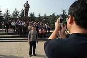 SHAOSHAN, CHINA - 4 NOVEMBER 2005 - Tourists take photos in front of a Mao statue in his ancestral hometown. Legend has it that on a rainy morning in December 1993, as Chinese President Jiang Zemin unveiled the 6 metre-high bronze statue of the late Chairman, just as President Jiang was pulling the sheet off Mao's shining face, the sun came blazing through the clouds and, even stranger, the moon shone brightly.    Photo by Natalie Behring