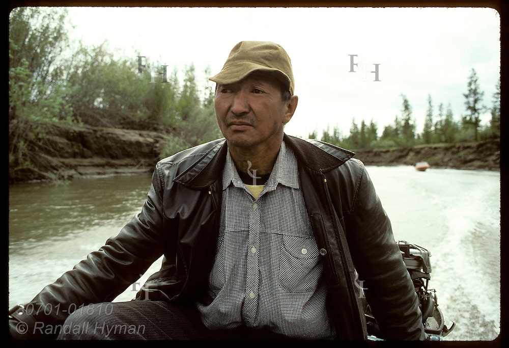 Sakha fisherman steadies outboard motor as he pilots boat down Adycha River in July; Yakutia. Russia