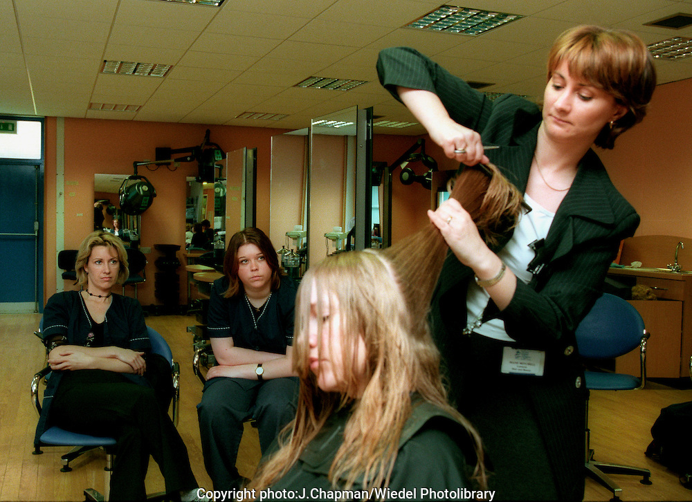 Further education  tutor demonstrating hair cutting and styling,