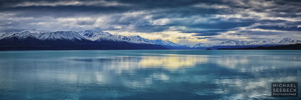 The aqua waters of Lake Pukaki are reflected in overhead clouds, in this panoramic photograph.<br /> <br /> LImited Edition of 125 Prints