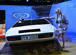 """© Licensed to London News Pictures. 08/09/2013. London, England. RM Auctions Classic Car auction at Battersea Evolution, London. Photo credit : Mike King/LNP. RM Auctions 8-9 September 2013 at Battersea Evolution. A car enthusiast named Johanna poseswith the 007 Lotus Esprit """"sumarine car"""". It is offered without reserve, but expected to sell for £650,000-£950,000."""