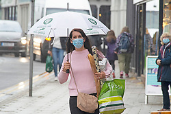 © Licensed to London News Pictures 04/06/2021. <br /> Sevenoaks, UK. A shopper getting wet in the rainy weather in Sevenoaks High Street in Kent. No more sunny weather today as the rain makes a comeback. Photo credit:Grant Falvey/LNP