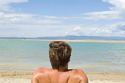 Back of head and shoulders of man sitting on a peaceful lakeshore in New Mexico