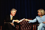 Washington DC 1997/08/13 President William Jefferson Clinton and First Lady Hillary Rodham Clinton pass a note during  a health care event.<br /><br />Photograph by Dennis Brack