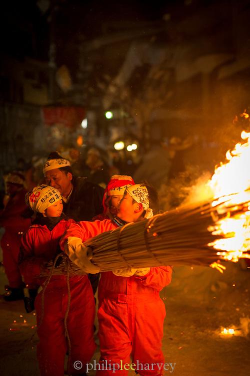 Two children holding burning straw at night, Nozawaonsen, Japan
