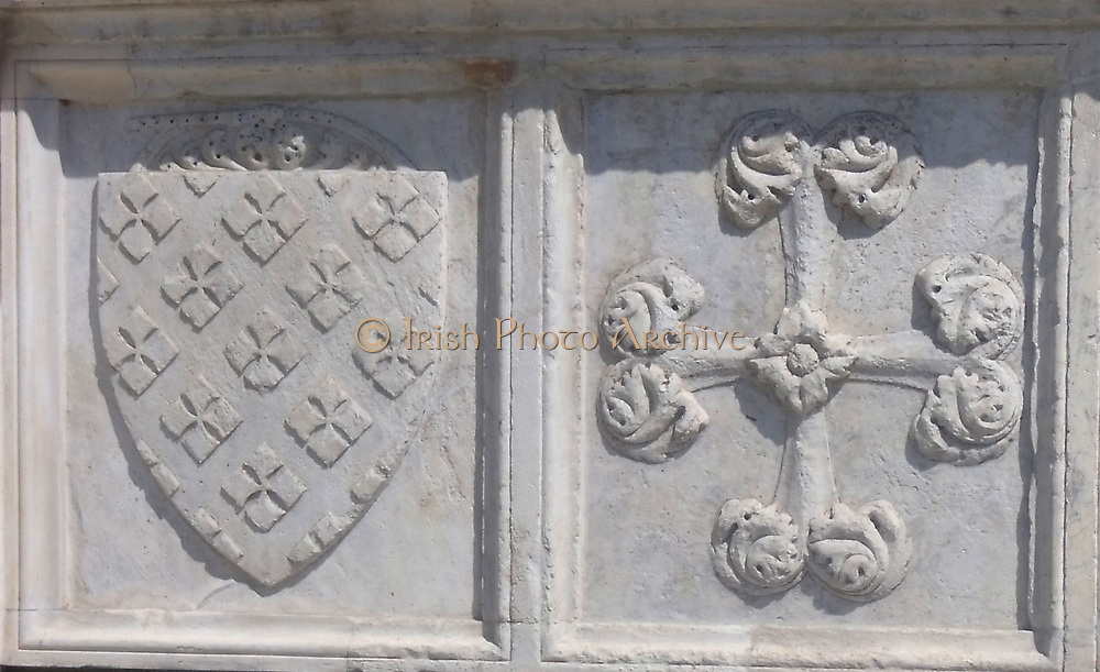 External detail from a church in Florence, Italy. Stonework reliefs, sculptures, and aesthetic embellishments adorn the outside of this church in Florence. This image shows a cross and a shield.