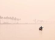 Man in canoe in the Kerala Backwaters, near Alappuzha, India