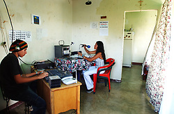 "Davis Semeco, left, plays music as Rosa Amarista, middle , hosts their radio show on ""A New Day Radio"", a community radio station in Caracas.  The station operates out of the home of Zulay Zerpa, who donates the space 7 days a week between 3pm and 9pm.  Chavez and his government have been increasingly supportive of these generally Chavista community media stations as a response to the anti-chavista private media."