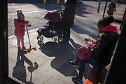 Young girl watches young smoker at a south London bus stop. As the older girl sits with a cigarette in her fingers, she taps on the phone keypad with blue smoke wafting up. The little girl strands next to her mother tipping up her scooter, looking at the behaviour of the other. Passive smoking can damage your body because secondhand smoke contains more than 4,000 chemicals, many of which are irritants and toxins, and some of which are known to cause cancer.