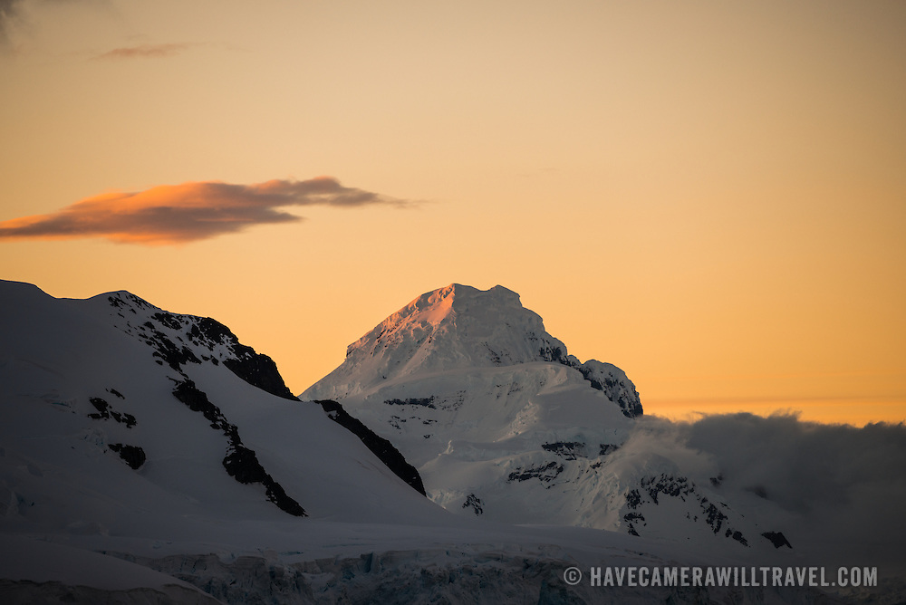 The setting sun casts a beautiful orange glow in the sky behind a mountain range in Paradise Harbor, Antarctica.