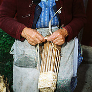 An elderly Romanian peasant farmer weaves a basket made from dried maize stems, Chendu, Romania