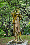 Statue of the Roman goddess Diana at Allerton Garden, on the south shore of Kauai, Hawaii, USA. In Roman mythology, Diana was the goddess of the hunt, the moon, and nature (associated with wild animals, woodland, and talking to and controlling animals), and virgin goddess of childbirth and women. She was one of the three maiden goddesses, along with Minerva and Vesta, who swore never to marry. Although she was eventually conflated with the Greek goddess Artemis, she arose independentently in Italy. Deer and oak groves were especially sacred to her. According to mythology (in common with the Greek religion and their deity Artemis), Diana was born with her twin brother, Apollo, on the island of Delos, daughter of Jupiter and Latona. Nestled in a valley transected by the Lawai Stream ending in Lawai Bay, Allerton Garden is one of five gardens of the non-profit National Tropical Botanical Garden (ntbg.org). Address: 4425 Lawai Rd, Koloa, HI 96756.