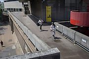 Two women run for their bus along the concrete walkway at the Southbank's Royal Festival Hall, on 15th June 2019, in London, England.