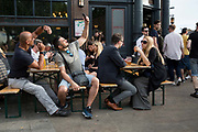 Customers using mobile phones at the busy The Cat And Mutton pub on Broadway Market on 27th May 2017 in London, United Kingdom. Broadway Market is an east London street running from London Fields to the Regents Canal in the London Borough of Hackney. From the series Our Small World, an observation of our mobile phone obsessions