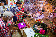 People pray in front of a doll that represents the Baby Jesus in a nativity scene during Christmas services at Holy Redeemer Church in Bangkok. Thailand is predominantly Buddhist but Christmas is widely celebrated throughout the country. Buddhists mark the day with secular gift giving but there are about 300,000 Catholics in Thailand who celebrate religious Christmas. Catholics first came to Thailand (then Siam) in 1567 as chaplain for Portuguese mercenaries in the employ of the Siamese monarchy. There has been a continuous Catholic presence in Thailand since then.