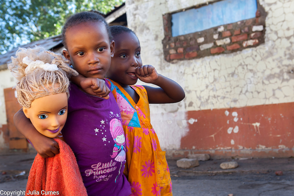 """Two little girls and a doll's head are photographed at Durban Deep's old """"Skomplaas"""" hostel on the outskirts of Johannesburg, South Africa.<br /> While the gold mine was still operating, the hostel housed hundreds of goldminers. Today a large number of families live in the crumbling buildings. Sanitary facilities are very poor and rats abound."""