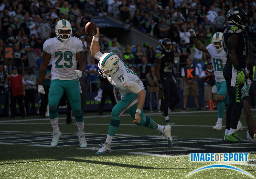 Sep 11, 2016; Seattle, WA, USA; Miami Dolphins quarterback Ryan Tannehill (17) spikes the ball in celebration after scoring on a 2-yard touchdown run in the fourth quarter against the Seattle Seahawks during a NFL game at CenturyLink Field. The Seahawks defeated the Dolphins 12-10.