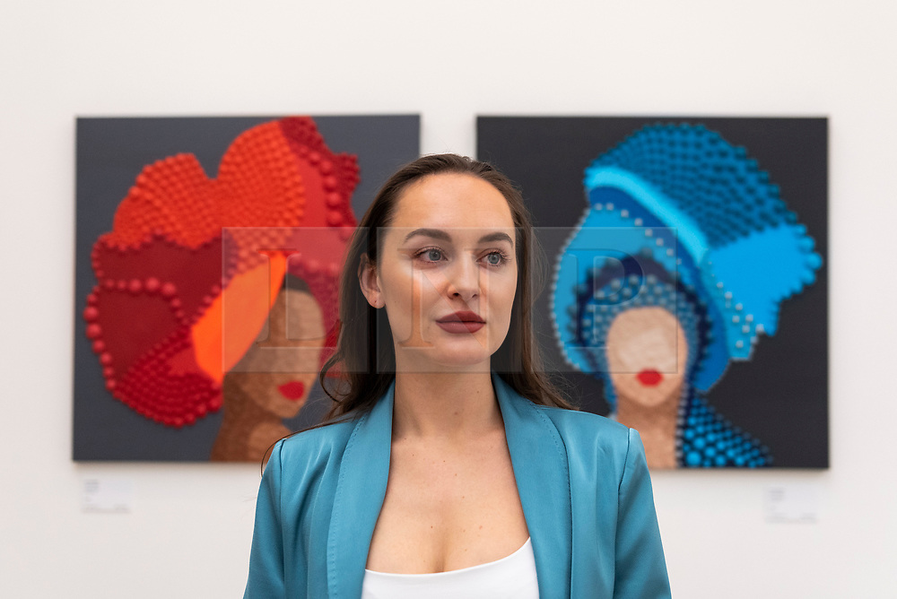 """© Licensed to London News Pictures. 14/10/2021. LONDON, UK. Artist Hannah Nijsten poses with her works (L) """"Fiery Soul"""", 2020, and """"Old Soul"""", 2020. Opening day of the eighth edition of START, an art fair presenting contemporary works by over 70 emerging international artists and galleries from over 25 countries.  The show runs to 17 October at Saatchi Gallery in Chelsea.  Photo credit: Stephen Chung/LNP"""