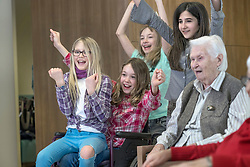 Girls celebrating success with senior women in rest home