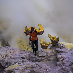 After cracking the hardened sulfur, the miners put them into bamboo baskets. 70-80 kilo is the average for one go. Some miners might carry up to 120 kilo. Cracked collarbones aren't unusual. When the sun rises they start carrying it up to the craters rim where they parked a trolley. With the trolley they roll up to 3 loads of sulfur down to the checkpoint. The checkpoint is 3 km away.