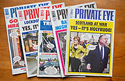 Front covers of editions of Private Eye satirical magazines viewed from above, UK