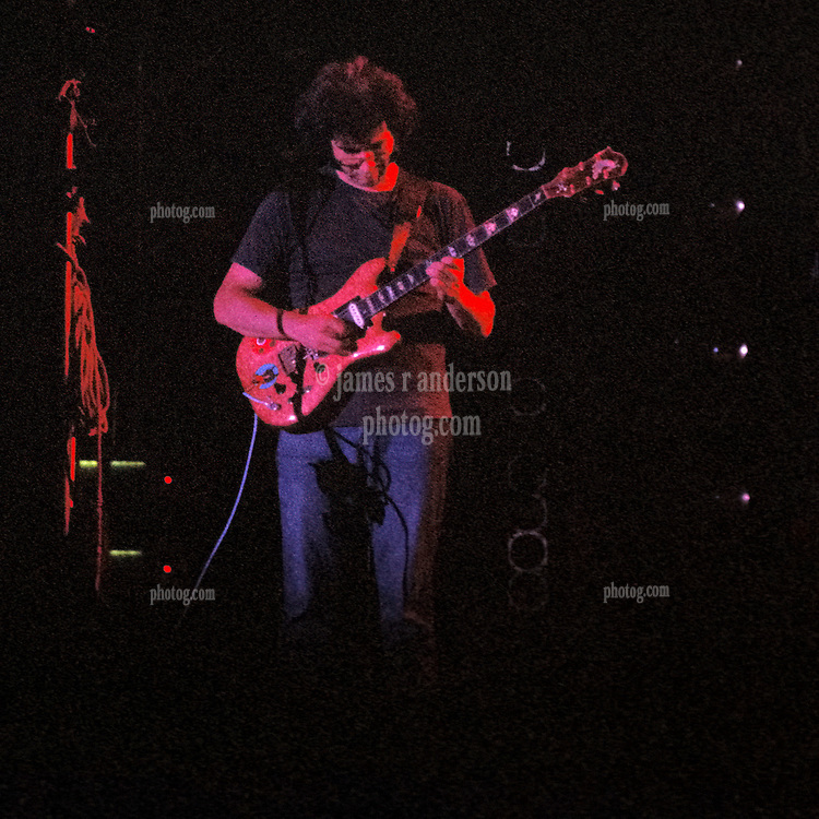 Jerry Garcia performing live with The Grateful Dead at Dillon Stadium, Hartford, CT 31 July 1974. Featuring the Wall of Sound. Summer weekday show, one of the longest ever played by The Dead. This night shot with only concert lighting probably during a jam in the third set.
