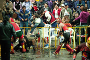 Male wrestlers and foreign travellers playing and wrestling with water out of ring. Lucha Libre wrestling origniated in Mexico, but is popular in other latin Amercian countries, including in La Paz / El Alto, Bolivia. Male and female fighters participate in the theatrical staged fights to an adoring crowd of locals and foreigners alike.