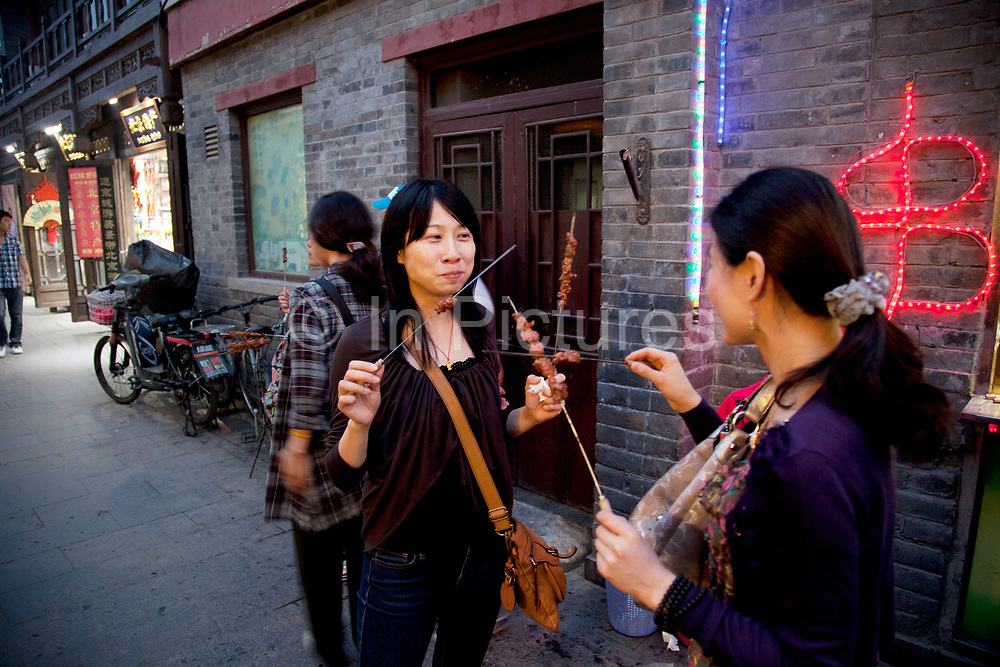 Eating pork skewers on Yandaixiejie Street (meaning Tobacco Pipe Lane) in Beijing, China. Located near to Houhai in downtown Beijing, Yandai Xiejie Street is a Hutong which attracts many tourists at day and night to it's souvenir shops and towards the bar area it leads to.