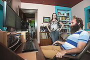 Dane Waters, center, and Kris Abplanalp, right, consider instrumental tracks on the computer in the upstairs bedroom while her husband Warren Gray changes their daughter Solvieg's diaper down the hall, left, as they work on a recording for Sapat, a collective musical group they all contribute to, Wednesday, July 16, 2013 in Louisville, Ky. (Photo by Brian Bohannon/www.brianbohannon.com)